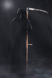 Death with scythe standing at night Royalty Free Stock Image