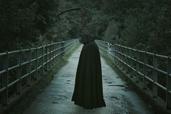 Death with scythe waiting on a  bridge. Hooded man with scythe waiting on a country bridge . Halloween and horror Royalty Free Stock Images