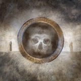 Death Spirit. Human skull enclosed within a corroded ring of mysterious carved runic symbols against a background of an ancient megalithic stone circle monument Stock Photos