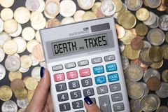 Death and taxes phrase on calculator's display, suggesting that nothing is certain but death and taxes, English expression royalty free stock photography