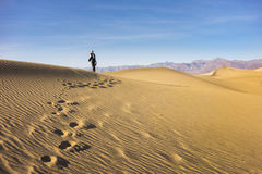 Death Valley Dunes. Woman walking along through the rippling golden sand of Mesquite Flat Dunes, Death Valley Stock Photo