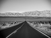 Death Valley, Mojave Desert lone empty road, California, USA: The hottest place on the planet Earth, black and white art photo. Death Valley, Mojave Desert road royalty free stock photo