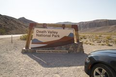 Death Valley National Park entrance signpost, American fast sport car parked in front, road trip in California USA royalty free stock photo
