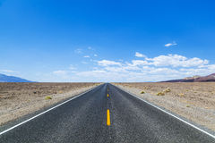 Death Valley road straight across. The desert to the mountains in the distance Royalty Free Stock Images