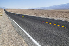 Death Valley road straight across the desert to the mountains in Stock Photo