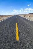 Death Valley road straight across the desert to the mountains Stock Photo