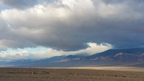 Death Valley salt flats with menacing clouds Royalty Free Stock Photo