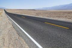 Death Valley vägraksträcka över öknen till bergen in Arkivfoto