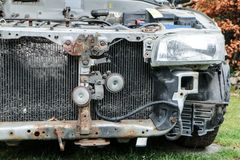 Deatil of the front of the car wreck. A detail of the old car wreck. The front of the car is visible, some parts are missing. The engine and radiator are without Royalty Free Stock Photos