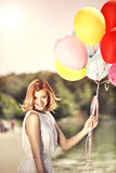 Deautiful girl with ballons. Young beautiful girl with colorful ballons in the park Stock Images