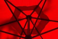 Debaixo de um guarda-chuva vermelho Fotos de Stock Royalty Free