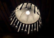 Debajo de la lámpara iluminada adorne con la bifurcación y el cuchillo de la cuchara Fotos de archivo
