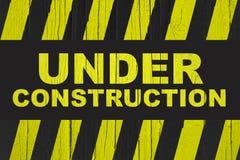 Debajo de señal de peligro de la construcción con amarillo y de las rayas negras pintadas sobre la madera agrietada imagen de archivo libre de regalías