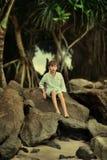 Debajo de un árbol en una roca grande sienta a un muchacho Imagen de archivo