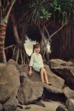 Debajo de un árbol en una roca grande sienta a un muchacho Imagenes de archivo