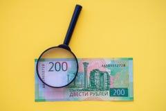 Debajo de una lupa que mira un billete de banco de 200 rublos para la autenticidad imagen de archivo
