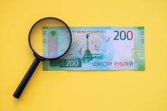 Debajo de una lupa que mira un billete de banco de 200 rublos para la autenticidad imagenes de archivo