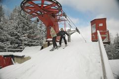 Debarking the Chair. Skiier and Snowboarder debarking the chairlift royalty free stock photo