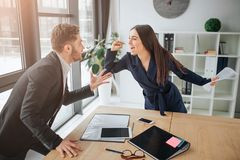 Debatteer tussen de jonge mens en vrouw Zij gilt en vecht met kerel Zij bevinden zich in ruimte bij lijst Materialen die op burea royalty-vrije stock foto's