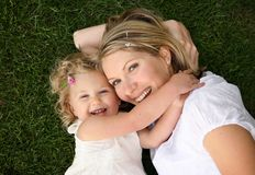 Debbrooke. Attractive and young white mother and her daughter lying on the grass smiling and playing together Stock Photography