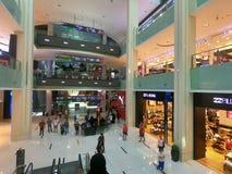 Debenhams, Billabong och kuguar shoppar på den Dubai gallerian - den inre sikten av den största shoppinggallerian för världar royaltyfri fotografi
