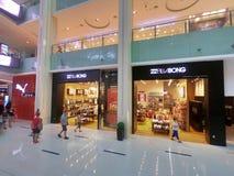 Debenhams, Billabong y tiendas del puma en la alameda de Dubai - vista interior del centro comercial más grande de los mundos foto de archivo