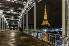 On the Debilly Bridge Eiffel Tower at Night and. Loving couple walking on the Debilly gateway over the Seine river and the Eiffel Tower at Night in Paris Stock Photos