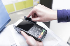 Debit card swiping on pos terminal. Royalty Free Stock Photography