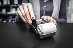 Debit card swiping on pos terminal. Stock Photo