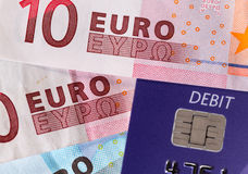 Chip and pin debit card on macro of euro. Debit word on plastic card on euro note suggesting debt problems in Europe Royalty Free Stock Photography