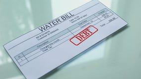 Debito della fattura di acqua, mano che timbra guarnizione sul documento, pagamento per i servizi, tariffa video d archivio