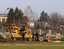 Debowiec/Polen - mars 27, 2018: Fjädra lokalvård av det gröna territoriet i staden Traktor och grävskopa för förbättring av gräsp Fotografering för Bildbyråer