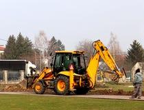 Debowiec/Polen - mars 27, 2018: Fjädra lokalvård av det gröna territoriet i staden Traktor och grävskopa för förbättring av gräsp Royaltyfri Foto