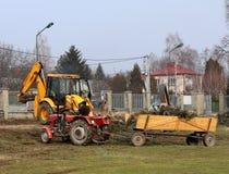Debowiec/Polen - mars 27, 2018: Fjädra lokalvård av det gröna territoriet i staden Traktor och grävskopa för förbättring av gräsp Arkivbilder
