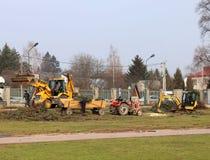 Debowiec/Polen - mars 27, 2018: Fjädra lokalvård av det gröna territoriet i staden Traktor och grävskopa för förbättring av gräsp Royaltyfri Fotografi