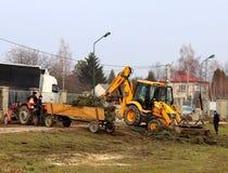 Debowiec/Polen - mars 27, 2018: Fjädra lokalvård av det gröna territoriet i staden Traktor och grävskopa för förbättring av gräsp Royaltyfri Bild