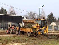 Debowiec/Polen - mars 27, 2018: Fjädra lokalvård av det gröna territoriet i staden Traktor och grävskopa för förbättring av gräsp Arkivfoton