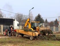 Debowiec/Polen - mars 27, 2018: Fjädra lokalvård av det gröna territoriet i staden Traktor och grävskopa för förbättring av gräsp Royaltyfria Bilder