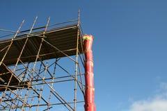Debris chute and scaffolding. Plastic debris chute and scaffolding at construction site Stock Photo