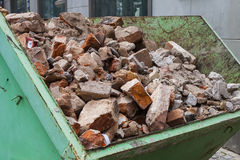 Debris in a green metal container. Stock Photos