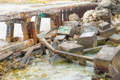 Debris and remains of collapsed bridge. Scattered concrete and steel debris and rubble of  partly collapsed bridge over water Royalty Free Stock Photography