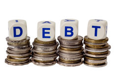 Debt. Stacks of coins with the word DEBT isolated on white background Royalty Free Stock Image