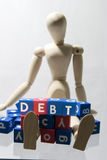 Debt. Wooden figure with a white back ground Stock Photo