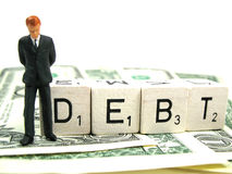 Debt. A businessman in debt in front of the word debt royalty free stock image