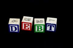 Debt. Building blocks with alphabets & numbers forming the word 'DEBT', isolated on a black background Royalty Free Stock Photography
