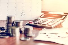 Debt collection and tax season concept with deadline calendar remind note,coins,banks,calculator on table. Background ,time to pay concept stock image