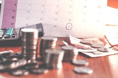 Debt collection and tax season concept with deadline calendar remind note,coins,banks,calculator on table. Background ,time to pay concept Stock Photo