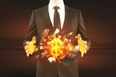 Debt concept. Businessman holding exploding wrecking ball with golden dollar sign inside on dark background Royalty Free Stock Photo