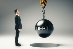 Debt concept. With businessman looking at wrecking ball hanging on crane hook. 3D Rendering stock photography
