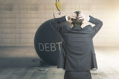 Debt concept. Stressed businessman with wrecking ball stock photo